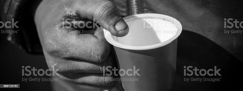 Dirty Beggar Hand Holding Plastic Cup. Poor Man Begging for Money on the Street Close Up. stock photo