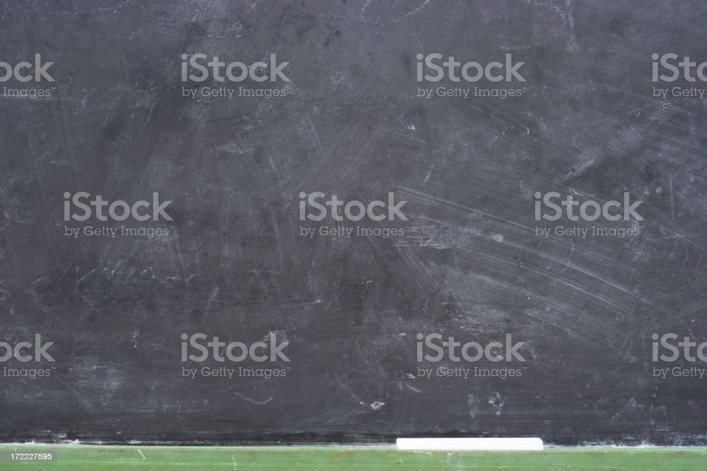 Dirty blackboard with chalk smudges and chalk at the bottom royalty-free stock photo