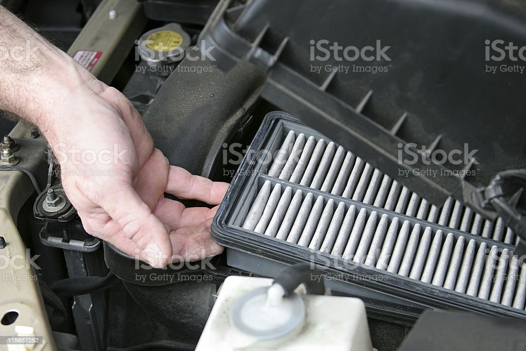 Dirty Car Air Filter An auto mechanic removing the dirty air filter from an automobile.   Photo taken as work was actually being performed. Adult Stock Photo