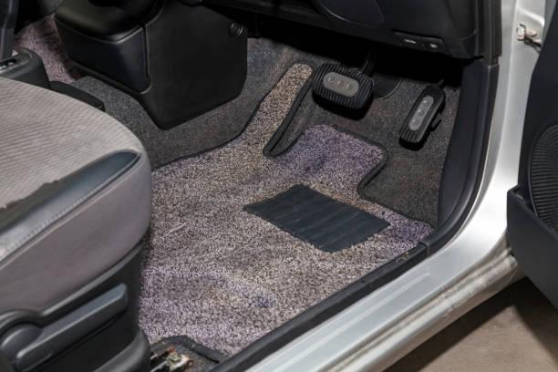 在乾洗前,在車間內為細節車輛提供帶油門踏板和制動器的灰色地毯的髒車地板墊。汽車服務業。轎車內飾。圖像檔