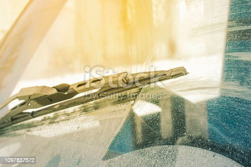 istock dirty car windshield with the included glass cleaner, in the big city front and back of the background is blurred 1097837572