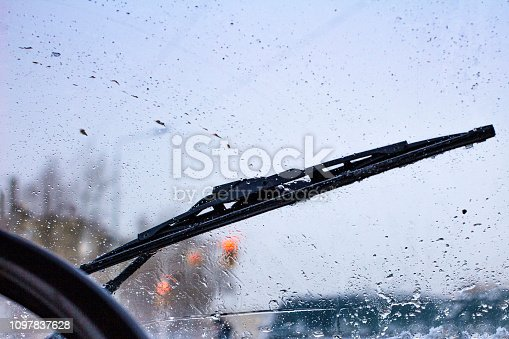 istock dirty car windshield with the included glass cleaner, in the big city front and back of the background is blurred 1097837628