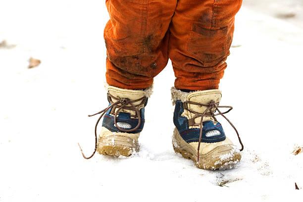 dirty child clothes - kinder winterstiefel stock-fotos und bilder