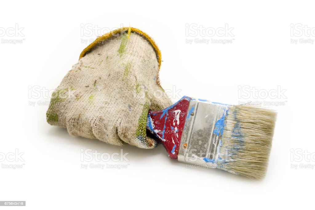 dirty cloth gloves hold used paint brush isolated on white background stock photo