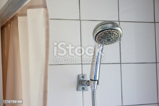 istock Dirty corroded limescale calcified shower head hanging from a stand inside cabin visible curtain 1216799169