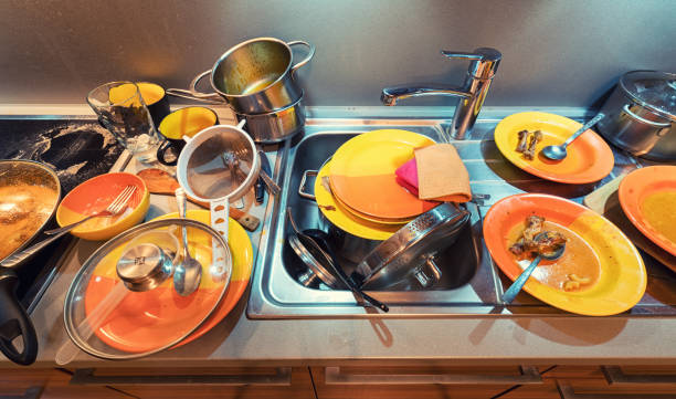 Dirty dishes in kitchen after cooking stock photo