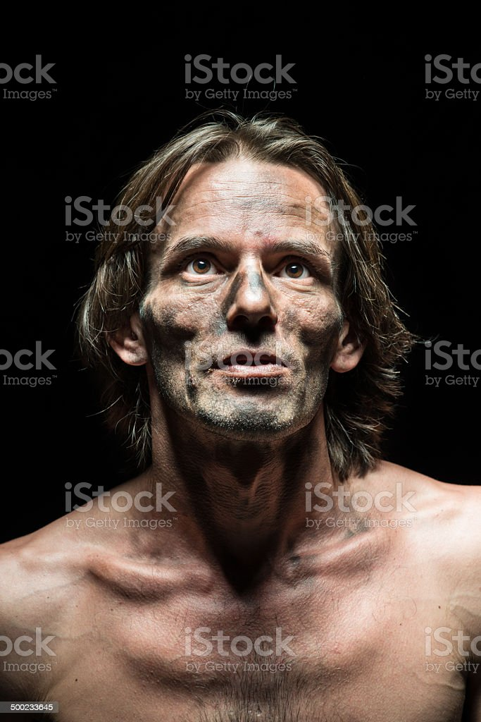 Dirty faced man looking up shirtless black background stock photo