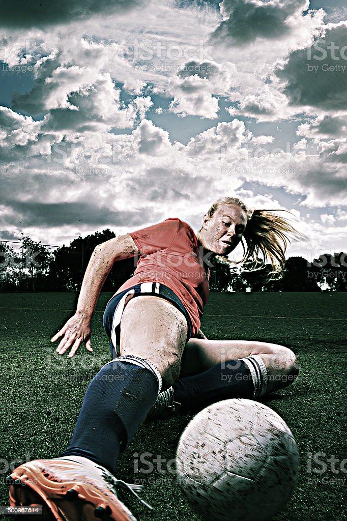 Dirty Female Soccer Player Sliding for the Ball stock photo