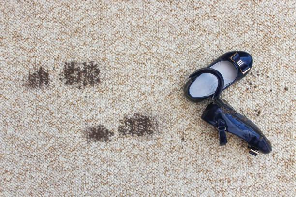 schmutzigen boden und kinderschuhe. konzept des kindes verschmutzt teppich. - fleckenentferner stock-fotos und bilder