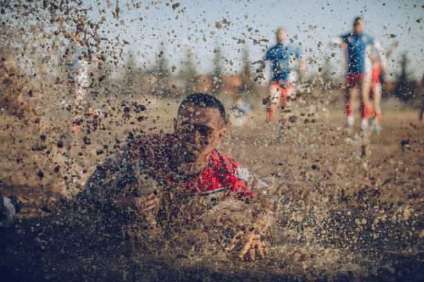 Dirty game Rugby players in action during the game. mud run stock pictures, royalty-free photos & images