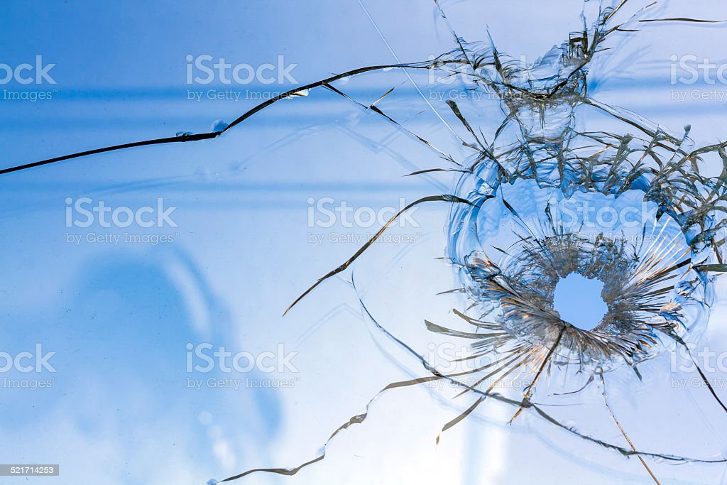 Dirty glass window with a bullet hole stock photo