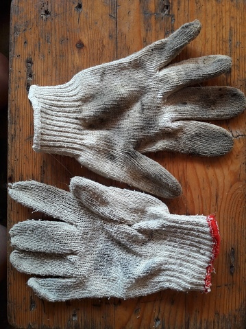 A pair of gloves, which is placed on a wooden table