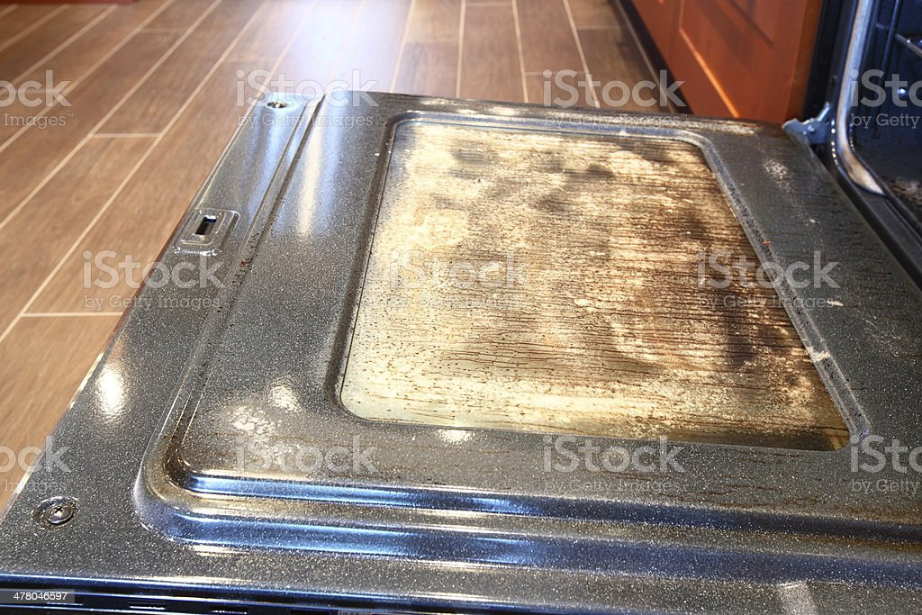Dirty greasy oven glass door being cleaned stock photo