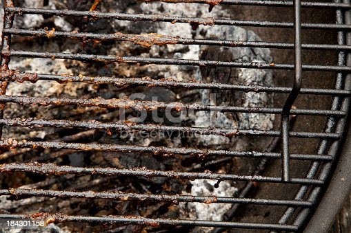Dirty barbeque grill with charred food particles.
