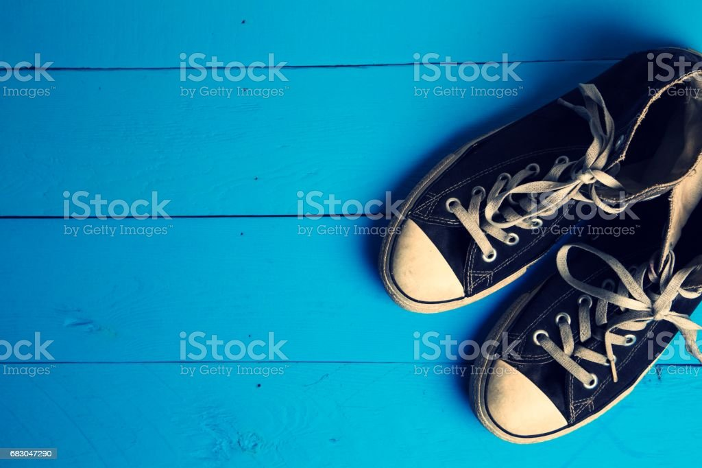 Dirty gumshoes on Blue wooden background foto de stock royalty-free