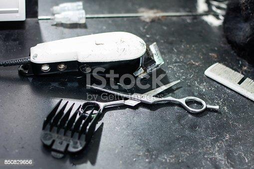 696318954 istock photo Dirty hair stylist tools on dark table 850829656