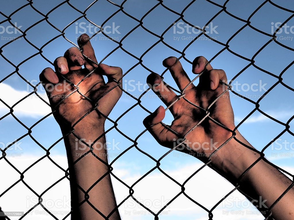 Dirty hands clinging to a steel wire fence stock photo