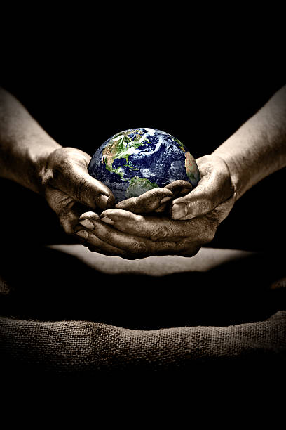 Dirty hands holding Earth stock photo