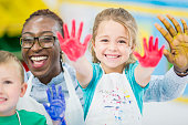 A multi-ethnic group of kids are indoors in a daycare center. They are wearing casual clothing while doing arts and crafts. A girl and her supervisor are showing their paint-covered hands to the camera.