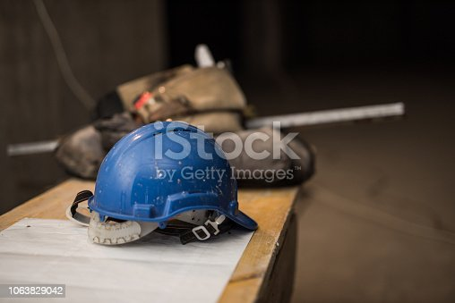 936384788 istock photo Dirty hardhat on a construction site. 1063829042