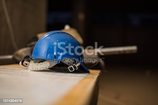 936384788 istock photo Dirty hardhat on a construction site. 1074304316