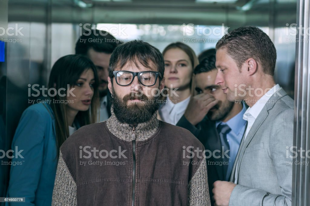 A dirty hipster affecting his coworkers in an elevator stock photo