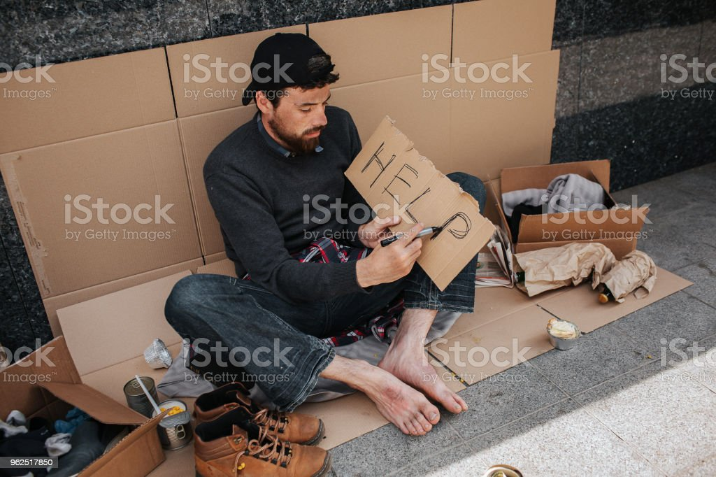 Mendigo sujo é sentado no cartão e a palavra ajuda a escrever em um pedaço de papel. Ele tem um monte de coisas no chão - Foto de stock de Adulto royalty-free