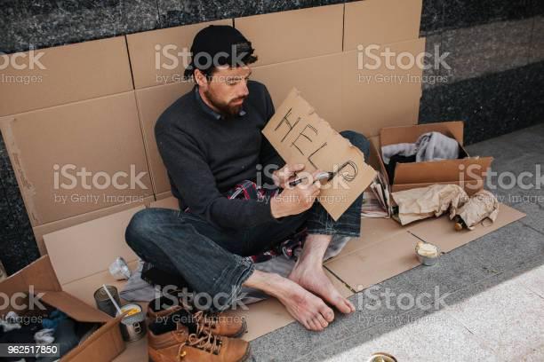 Foto de Mendigo Sujo É Sentado No Cartão E A Palavra Ajuda A Escrever Em Um Pedaço De Papel Ele Tem Um Monte De Coisas No Chão e mais fotos de stock de Adulto