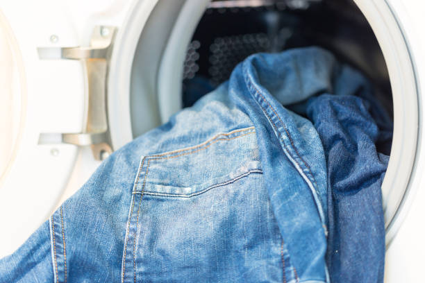 Dirty jeans trousers in washing mashine stock photo