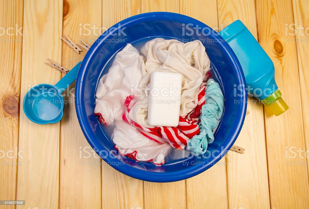 Dirty laundry in blue bowl with soap stock photo