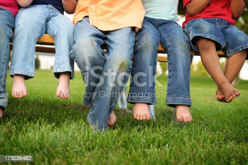 istock Dirty Legs and Feet of Children Sitting on a Bench 173036462