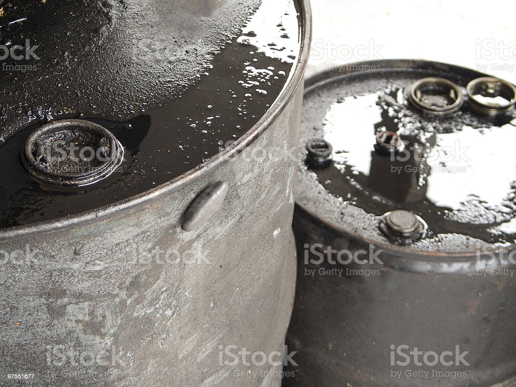 Dirty messy dripping black oil barrels closeup royalty-free stock photo