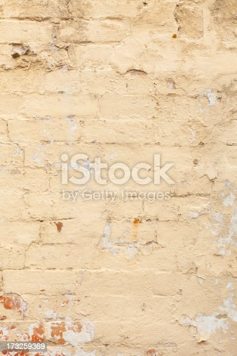 An old brick wall with peeling paint.