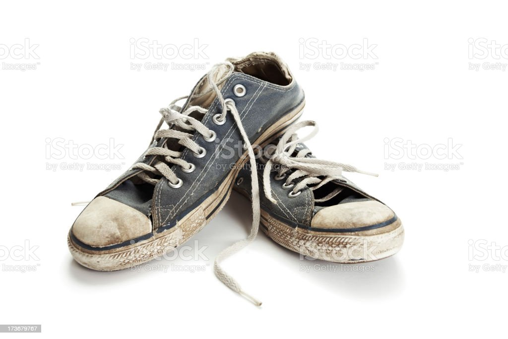Dirty old blue and white running shoes on a white background stock photo