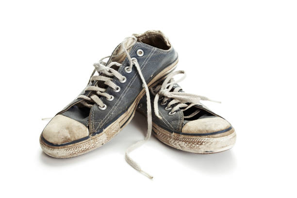 dirty old blue and white running shoes on a white background - dirty shoes stock photos and pictures