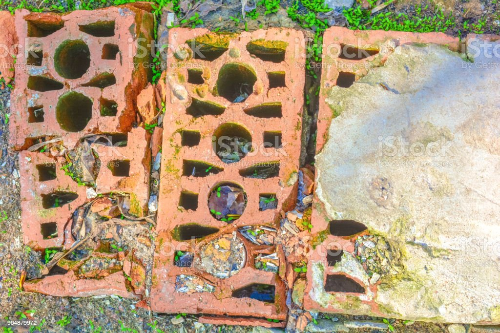 Dirty old cracked bricks on ground with green grass royalty-free stock photo