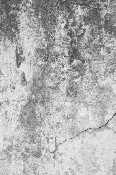 Schmutzige, alte Steinwand mit rauen und rissigen Strukturen. Unten rechts ein starker Riss in der Wand. Betonwand Hintergrund im Hochformat, im Industrial Design. – Foto
