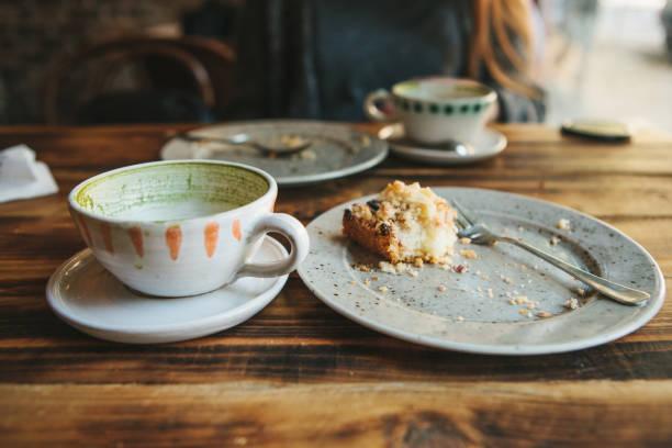 en smutsig skylt och en tom kopp kaffe. det halv-ätit cupcake på en tallrik. tomma skålar efter att ha ätit på ett träbord. på bakgrund av en flicka i ett café - tallrik uppätet bildbanksfoton och bilder
