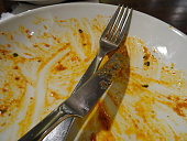 Photo showing a dirty plate with the remains of a meal with a rich, tomato based sauce / gravy - almost a clean plate, as everything has been eaten.  The round, white plate is pictured with a stainless steel knife and fork / cutlery at the end of a meal, where all of the food has been eaten.  The plate is ready to be added to the ever growing pile of washing up in the kitchen.