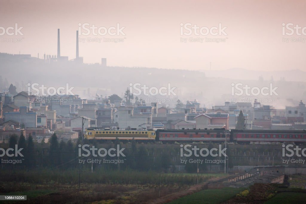 Dirty pollution. A train passes the old city of south Yunnan, China,...