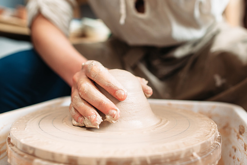 Dirty potter hand on potters wheel front view