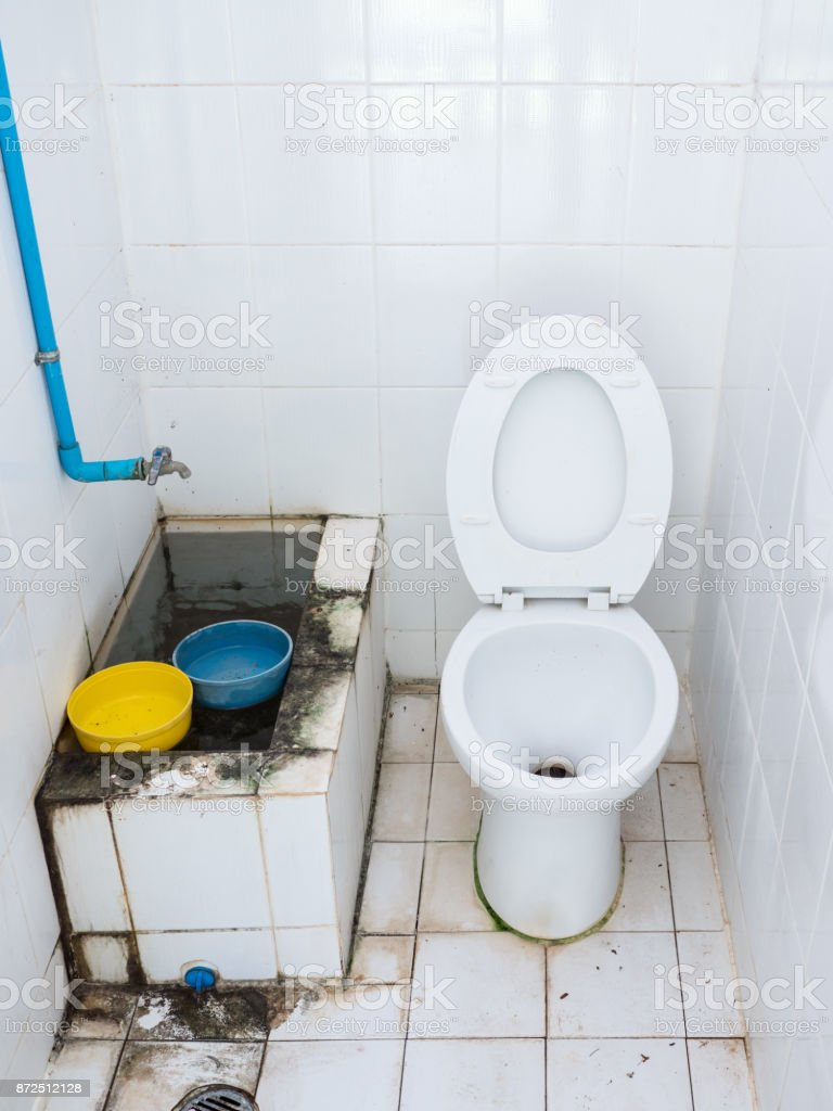 Dirty public toilet with the white tile. stock photo