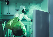 A funny depiction of a fridge that is long overdue to be cleaned.  A man wearing a hazardous materials clean suit and gas mask pulls things out and puts them into a yellow biohazard bag.  Smoke or steam pours from the the open refrigerator door.