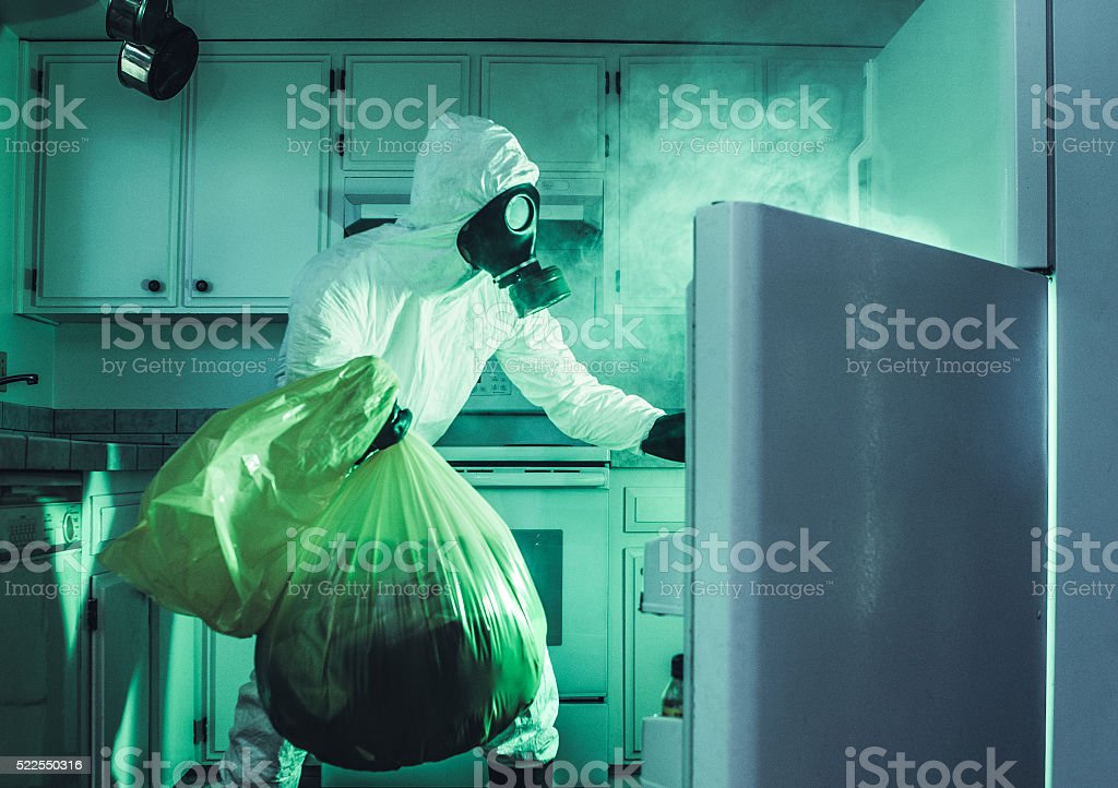Dirty Refrigerator Cleaning in Hazmat Suit stock photo