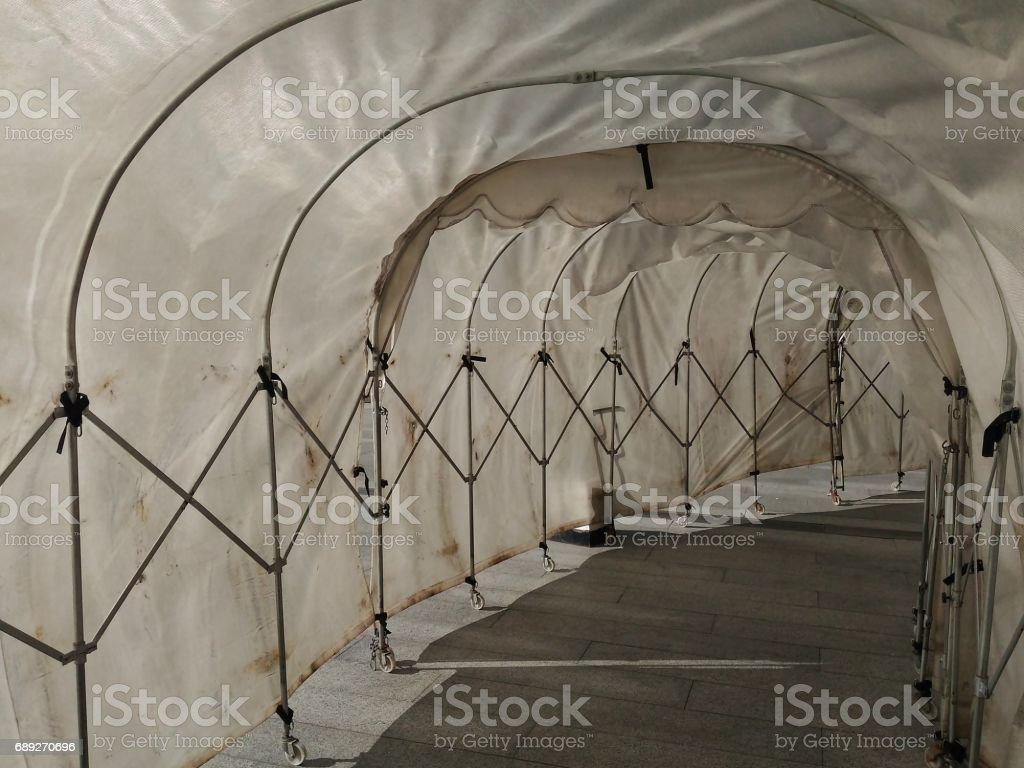 dirty retractable Industrial Tunnel walkway shade and wet protector from rain for outdoor walkway stock photo