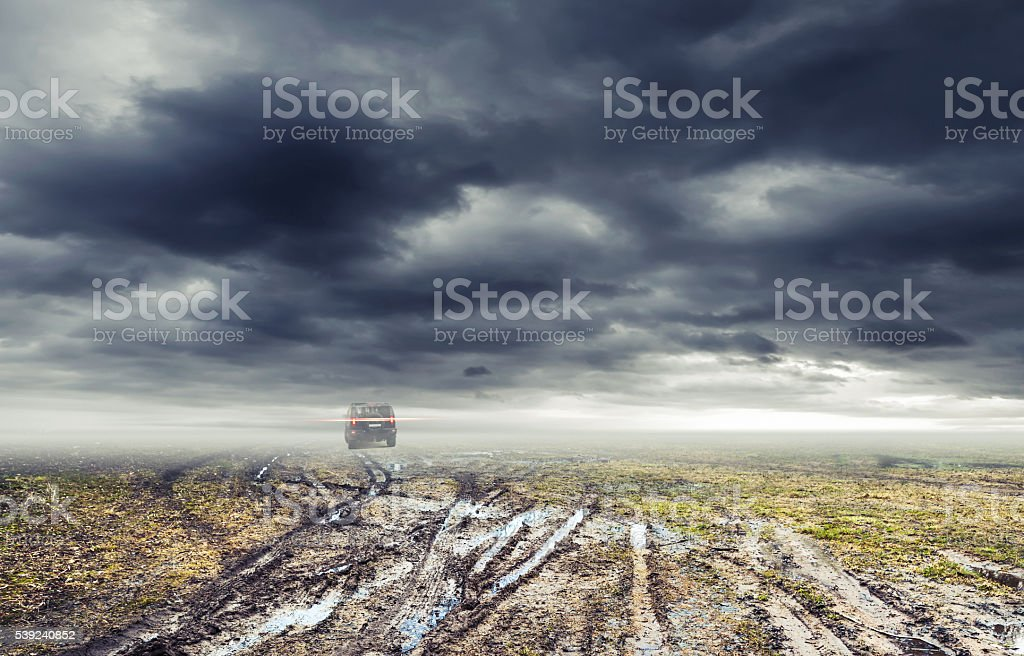 Dirty road with puddles, suv car goes far away stock photo