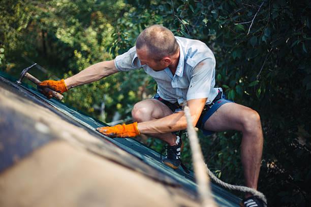 dirty roofer installs bitumen roof shingles - dachschräge einrichten stock-fotos und bilder
