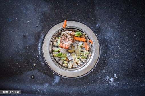 A dirty sink with leftover food bits that clog up the flow of water.