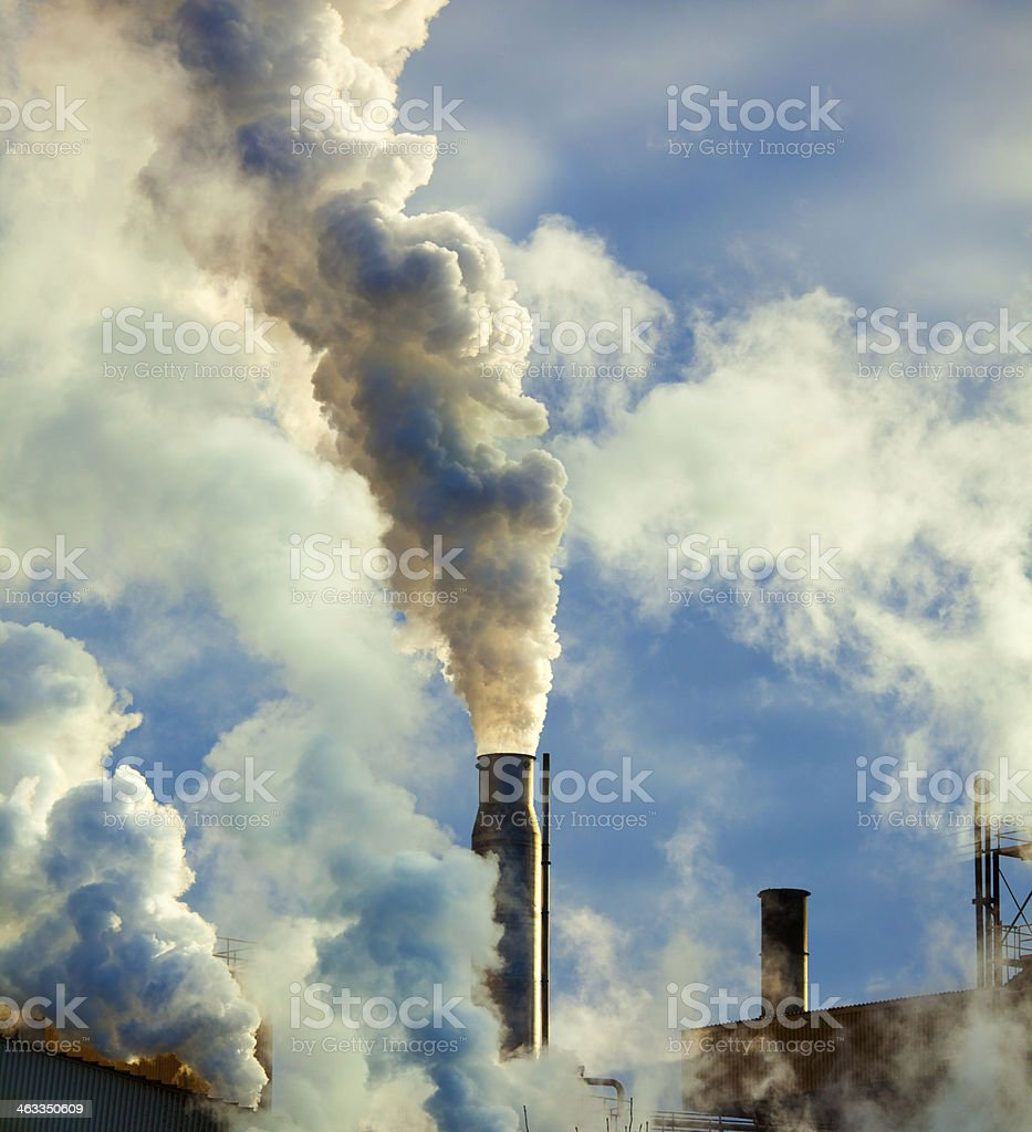 Dirty Smoke Stacks Belch Carbon and Pollution into the Atmosphere stock photo