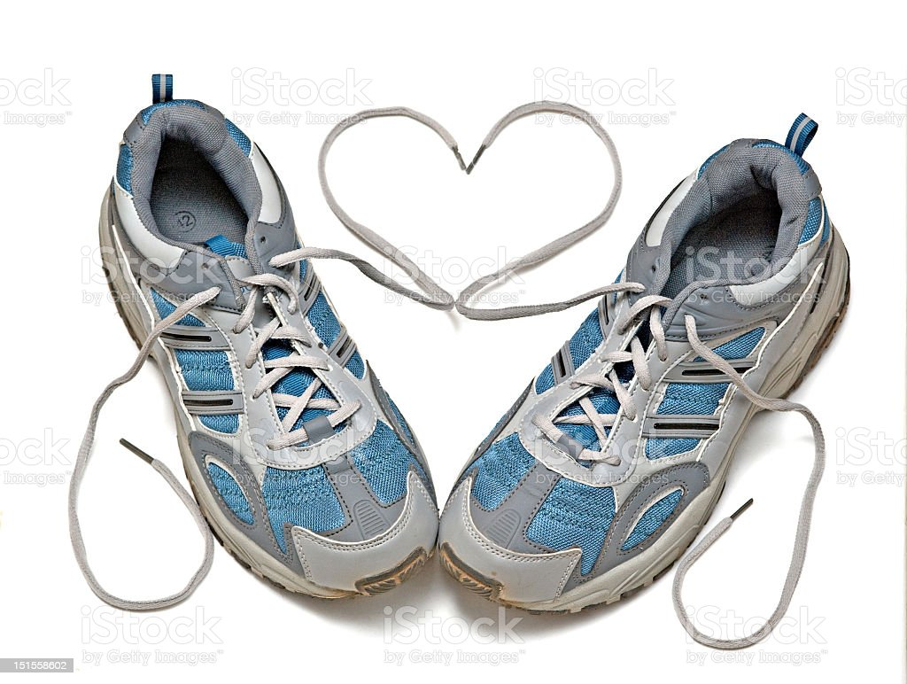 Dirty sneakers with laces forming heart on white background stock photo